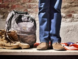 Military boots and bag next to man standing, only picturded knees down