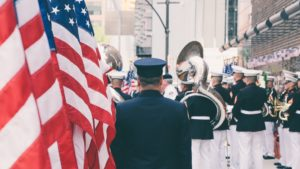 Man in uniform with a parade, american flag in forefront of image